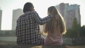 O indivíduo e a menina sentam-se no banco e no olhar de rio na cidade video estoque