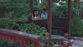 O indivíduo e uma menina estão sentando-se no parque filme