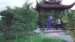 O indivíduo e uma menina estão sentando-se no parque video estoque