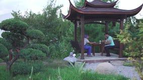 O indivíduo e uma menina estão sentando-se no parque vídeos de arquivo