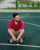 O indivíduo elegante considerável de sorriso vestiu-se em uma camisa vermelha e no short que sentam-se em um skate no campo de bá Imagem de Stock
