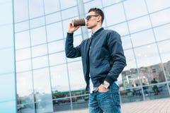O indivíduo em óculos de sol à moda, um homem anda em torno da cidade e o café bebendo de um copo de papel, um indivíduo consider Foto de Stock