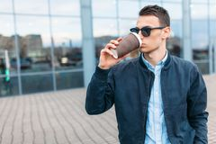O indivíduo em óculos de sol à moda, um homem anda em torno da cidade e o café bebendo de um copo de papel, um indivíduo consider Foto de Stock Royalty Free