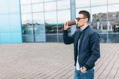 O indivíduo em óculos de sol à moda, um homem anda em torno da cidade e o café bebendo de um copo de papel, um indivíduo consider Imagens de Stock