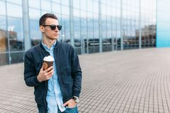 O indivíduo em óculos de sol à moda, um homem anda em torno da cidade e o café bebendo de um copo de papel, um indivíduo consider Fotos de Stock Royalty Free