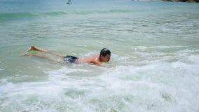 O indivíduo encontra-se na praia e nada-se nas ondas do mar em um dia ensolarado vídeos de arquivo