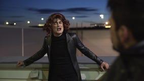 O indivíduo engraçado cômico vestido como a mulher, a roupa preta vestindo e a peruca, canta a parte externa vídeos de arquivo