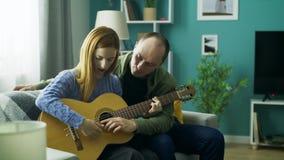 O indiv?duo ensina a menina jogar a guitarra em sua sala de visitas