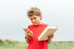 O indivíduo escolhe entre um livro e um smartphone Fotos de Stock