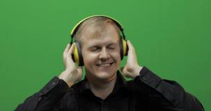 O indivíduo escuta a música em fones de ouvido amarelos sem fio e em danças Tela verde filme