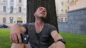 O indivíduo escuta música no telefone que senta-se sob uma árvore no estacionada sob uma árvore video estoque