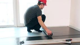 O indivíduo especializado com capacete vermelho coloca a esteira do secundário-revestimento no apartamento novo video estoque