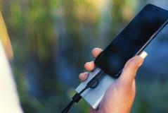 O indivíduo está guardando um carregador portátil com um smartphone em sua mão Homem em um fundo da natureza com umas hortaliças  Imagens de Stock Royalty Free