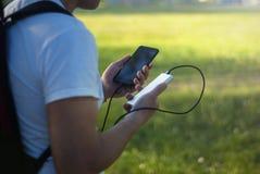 O indivíduo está guardando um carregador portátil com um smartphone em sua mão Homem em um fundo da natureza com verdes imagem de stock
