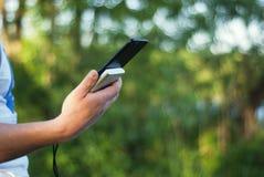 O indivíduo está guardando um carregador portátil com um smartphone em sua mão Homem em um fundo da natureza com verdes Fotografia de Stock