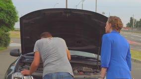 O indivíduo está na frente do carro e do olhar sob a capa A menina dá-lhe a chave Dá-o de volta à mulher Dá-o outro video estoque