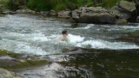 O indivíduo está nadando no rio Um indivíduo bonito novo banha-se em um rio limpo da montanha Está feliz filme