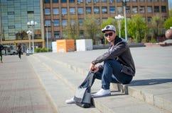 O indivíduo está sentando-se na rua Fotos de Stock