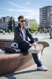 O indivíduo está sentando-se na rua Imagem de Stock