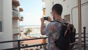 O indivíduo está tomando a foto da vista de surpresa do balcão usando a câmera do telefone celular vídeos de arquivo
