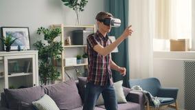 O indivíduo excitado está tendo o divertimento com os óculos de proteção da realidade virtual que vestem os auriculares e os braç filme