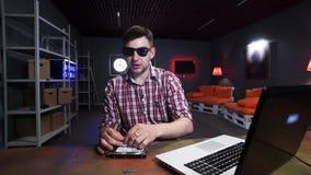 O indivíduo fala na câmera que coloca o cartão flash, o HDD, o cartão de memória e o portátil na mesa video estoque