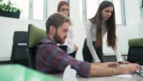 O indivíduo farpado alegre e duas moças estão discutindo o plano de trabalho no escritório no local de trabalho O alto diretivo video estoque