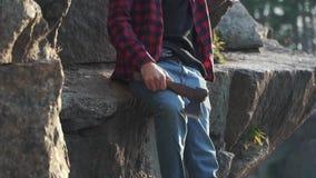 O indivíduo farpado com machado senta-se perto da pedra enorme e da vista na distância Homem sério brutal com machado fora filme