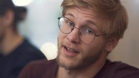 O indivíduo farpado com vidros compartilha de suas impressões que transportam suas emoções da reunião na tabela da discussão com  video estoque