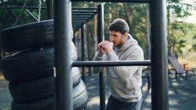 O indivíduo farpado forte está encaixotando apenas fora usando pneus na esporte-terra durante o exercício no dia de verão exercit filme