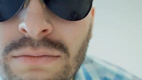O indivíduo farpado sério nos óculos de sol está sorrindo, fim acima, emoção humana do conceito filme
