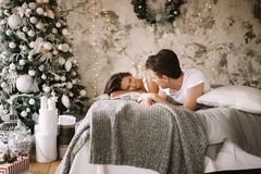 O indivíduo feliz e a menina vestidos nos t-shirt brancos estão encontrando-se em uma cama e estão olhando-se se imagem de stock