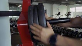 O indivíduo forte pendura placas do peso no lugar vídeos de arquivo