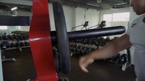 O indivíduo forte pendura placas do peso no lugar filme