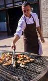O indivíduo frita salsichas bávaras em uma grande grade imagens de stock