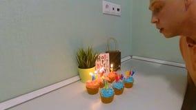 O indivíduo funde para fora as velas de seus queques festivos em honra de sua festa de anos vídeos de arquivo