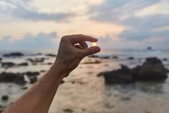 O indivíduo guarda o sol do por do sol em suas mãos imagem de stock