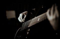 O indivíduo joga a guitarra, preto no foco branco, macio, fim acima Imagens de Stock Royalty Free