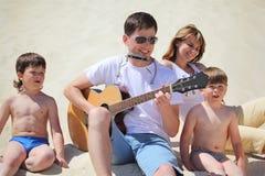 O indivíduo joga o acordeão da guitarra e do bordo com crianças fotografia de stock