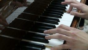 O indivíduo joga o piano Mãos de uma imprensa do homem novo as chaves brancas e pretas de um instrumento musical Um pianista novo video estoque