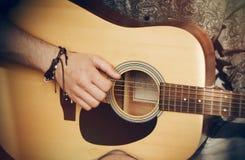 O indivíduo joga uma guitarra acústica ao estilo dos anos 80 foto de stock royalty free