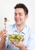 O indivíduo latino-americano de riso em um sofá ama a salada verde Imagens de Stock Royalty Free