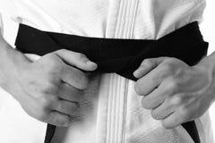 O indivíduo levanta no quimono branco com cinturão negro, fim acima Imagens de Stock