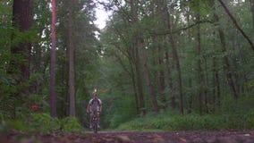 O indivíduo monta uma bicicleta fora das madeiras vídeos de arquivo