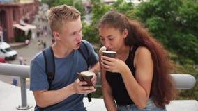 O indivíduo mostra algo a sua amiga na tela do smartphone na rua da cidade vídeos de arquivo