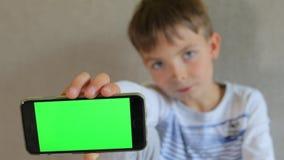 O indivíduo mostra o smartphone, guarda à disposição vídeos de arquivo