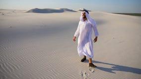 O indivíduo muçulmano alegre do xeique dos UAE do Arabian anda com as extensões do deserto com sorriso na cara no dia de verão cl filme