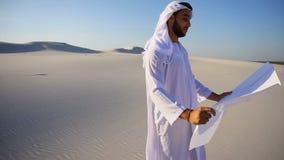 O indivíduo muçulmano sábio da construção do xeique dos UAE do Arabian inspeciona a área e lê o modelo para a construção, estando filme
