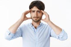 O indivíduo não pode concentrar-se e centrar-se sobre o trabalho como ter a enxaqueca ou a dor de cabeça que smirking virou guard imagens de stock