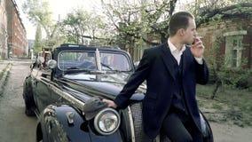 O indivíduo na imagem de um gângster senta-se no carro e fuma-se filme